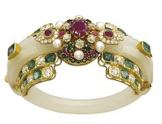 A JADEITE, MULTI-GEM AND DIAMOND BRACELET, BY CARTIER & BY LOMBARD  Designed as a carved jadeite band with emerald and ruby details, the front bordered by emerald and diamond twin lines, centering upon a later ruby, emerald, cultured pearl and diamond bombé cluster with ruby and diamond foliate shoulders, 17.0 cm inner circumference, with French assay mark for gold With maker's mark for Cartier