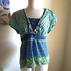 Patterned crochet blouse It has a really pretty blue floral print. It also has a lot of green in it. It has blue crochet accents at the neckline and waist. It ties at the back. It has some beading at the neckline. 100% cotton. Dress Barn Tops Blouses