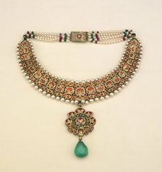 19thC    Materials: ruby, pearl, gold, enamel, emerald, diamond    Necklace of diamonds set in gold with pendant of diamonds and teardrop emerald. Pearls along edges of diamonds and in five rows at clasp, strung with rubies and emeralds. Enamel floral patterns on reverse. Thirty main diamonds.