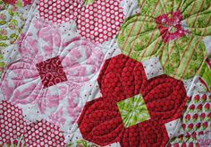 This is the snowball block.  Essentially you sew a smaller square to each of a larger square's corners creating an octagon shape. Notice that one of the square is different than the background fabric and that forms the center of the flower.