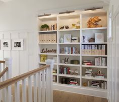 Top-of-the-stair landing rich in detail: board and batten siding, chunky balusters and built-in bookshelves. By Modern Organic Interiors.