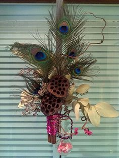 dried lotus pods, peacock feathers, Door Adornment with dried eucalyptus leaves and pods, cinnamon sticks, corylus branches, with attached glass bubble vase for a fresh flower!