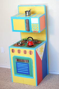 A do-it-yourself play kitchen I made for my kids. Find out what inspired me to make it, and get some tips on how to create this fun and cute play kitchen. Cardboard Kitchen, Cardboard Box Crafts, Cardboard Furniture, Cardboard Crafts, Cardboard Playhouse, Diy For Kids, Crafts For Kids, Diy Crafts, Play Kitchen Diy