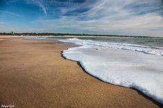 Un beau volume d'écume sur le sable vierge de trace