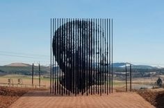 Mandela by Marco Cianfanelli  The sculpture, by artist Marco Cianfanelli, significantly comprises 50 steel column constructions – each between 6.5 and 9.5 metres tall – set into the Midlands landscape. The approach to the site, which has been designed by Jeremy Rose of Mashabane Rose Architects, leads one down a path towards the sculpture where a portrait of Nelson Mandela, looking west, comes into focus, the 50 linear vertical units lining up to create the illusion of a flat image.