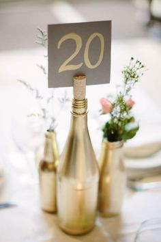 Gold painted wine glasses with cork table number card | 20 Vase Alternatives You Haven't Considered For Your Wedding Tablescape via @junebugweddings