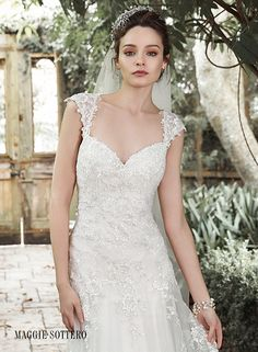 A gorgeous illusion back, adorned with embellished lace appliques, makes a statement in this otherwise understated lace A-line wedding dress, Almudena by Maggie Sottero.
