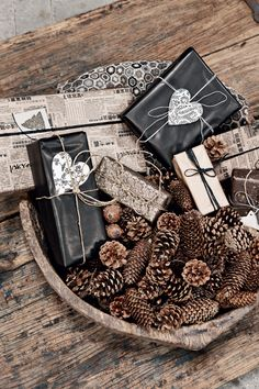 Asian newspaper wrapped presents in bowl w/ pine cones