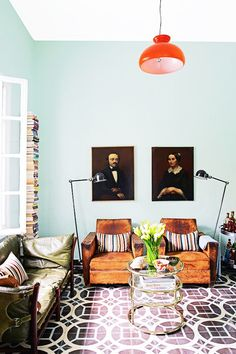 For a fun and funky living room style, pair vibrant and modern colors with traditional portrait paintings.