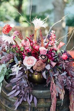 These centerpieces from Dirt Flowers incorporate beautiful shades of red, pink and purple that are perfect for Andrea and Aaron's Whimsical Boho wedding captured by Anna Smith Photography. #bridesofnorthtx #weddings #centerpieces