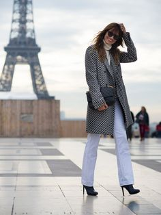Caroline de Maigret wears a turtleneck, checked coat, white jeans, boots, black sunglasses, and a Chanel bag