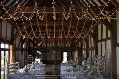 A huge multi-swag canopy for a stylish barn wedding at the exquisite Loseley Park #fairylights #weddingdecor