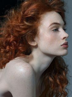 Girl with red curls and white opaque skin with freckles