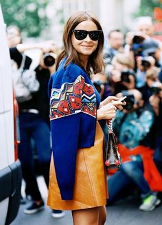 Miroslava Duma wearing a leather camel skirt with a cropped cobalt patterned jacket