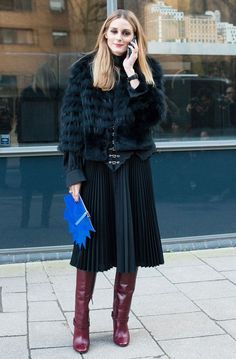 Olivia Palermo wears a black fur cropped jacket, pleated skirt, and knee-high boots