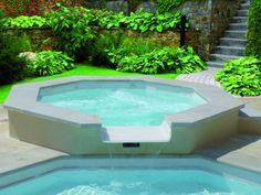 Mise en avant d'un Jacuzzi de forme octogonale avec versement dans la piscine extérieur. Ce Jacuzzi est du modèle Iris. La terrasse qui l'entour est en pierre naturelle de couleur clair.