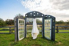 Glass windows and doors prop with wedding dress hanging from it (photo by Golightly Studios)