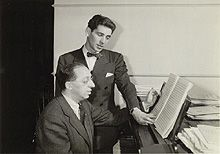 Bernstein reads music over the shoulder of Copland, seated at piano
