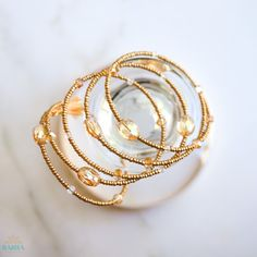 Champagne embodies the dazzling amber fizz and sparkle of a luxurious glass of bubbly. This spiral bangle is handmade with beautiful glass crystal beads and fine glass seed beads in shades of amber and gold.