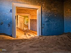 "This photograph was made in Kolmanskop, Namibia. Kolmanskop is an abandoned diamond mine near the coast. The ""ghost"" town has several residences and barrack-type accommodations, as well as the remains of a few commercial establishments. Today the town is a photographer's dream come true. One cannot spend enough time taking in all the photographic opportunities. For this photograph I had to crawl through a small opening in a window and have my friend pass my camera gear into me."