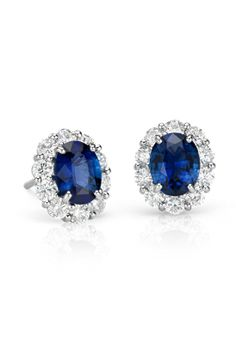 Iconic and stunning, these classic earrings showcase vibrant oval shaped sapphires framed by a brilliant halo of round diamonds set in 18k white gold   Gift Guide