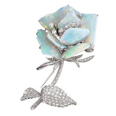 Australian Opal Diamond Brooch ,This exquisite flower brooch design features seven australian opals weighing 19.78 cts. total. The stem and leaves are encrusted with pave diamonds. In the center of the flower are three oval and two round brilliant diamonds. Handmade 18k white gold setting.