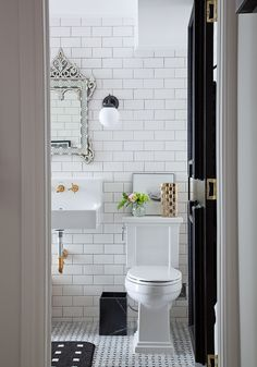 Nice toilet and sink White subway tile bathroom with black and gold accents