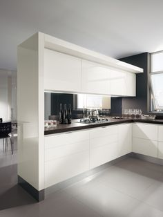 """The """"Mirage"""" partition viewed from the kitchen's working and service zone   There are no handles in the door front panels; in the modern Scenery kitchen, the units are opened by means of grooves or by handles set into the tops or sides of the fronts   #Kitchens   #Scavolini"""