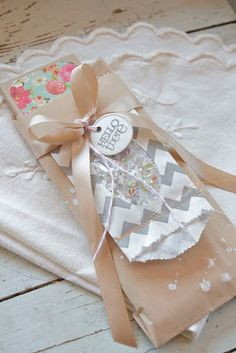 """I die cut an oval using my Papertrey oval dies and then just tucked in a plastic baggie that I had filled with confetti. To embellish the Kraft sack packaging I used a metal tag stamped with """"hello there"""" from Framed Out #2. The ribbon is Kraft Satin."""