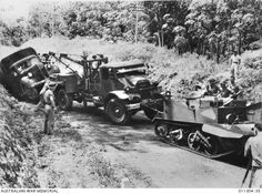 1942-01, MALAYA. FOLLOWING MONSOONAL RAINS A BOGGED INDIAN ARMY TRUCK IS ASSISTED BY AN AIF BREAK DOWN TRUCK AND A BRITISH BREN GUN CARRIER.