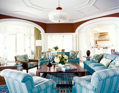 """""""We needed to give the family room its own identity to separate it from the open kitchen,"""" says Papachristidis. """"So we used quite a bit of fabric and painted the walls dark brown."""" Club chairs are covered in French Stripe in blue/gray by Kathryn M. Ireland; cushions on the Bielecky Brothers cane chair are Jasper's Tree of Life in sage; sofas are in Blandford in Old Blue by Colefax and Fowler through Cowtan & Tout. Curtains are Kasari ikat in Palm from Schumacher. Rug by Beauvais…"""