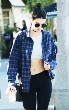 Kendall Jenner wears a velvet choker, crop top, plaid flannel, leggings, a black shoulder bag, and aviator sunglasses