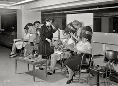 Detroit, Michigan: Women drying their hair in the beauty shop at the Crowley-Milner department store, July 1941.