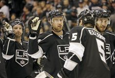 Los Angeles Kings center Jeff Carter, middle, is congratulated by teammates after the game in which he scored three goals, for a hat trick against the Nashville Predators in an NHL hockey game in Los Angeles Monday, March 4, 2013. The Kings won, 5-1. (AP Photo/Reed Saxon)