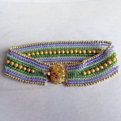 Czech seed beads in: purple with a fuchsia lining , clear with a dark green lining, and translucent light green with a rainbow finish. A gold trim finishes this elegant cuff bracelet.