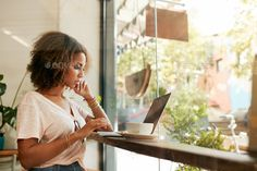 Young black woman at cafe using laptop by jacoblund. Young black female at cafe using laptop. African young woman sitting in a restaurant busy working on her laptop.