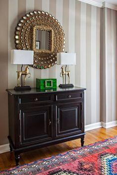 Design Manifest Hallway black chest, peacock mirror, Turkish rug, striped wall