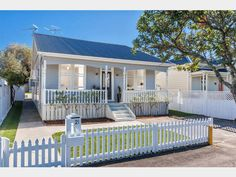 Picture perfect!! Outside view of wooden 3 bedroom 1910 cottage @ William Bond St, Devonport. Cute white picket fence, white roses, and white railed wood verandah. (in Jun 2014)