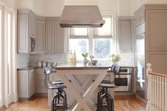 Cabinet paint color is Benjamin Moore Briarwood. A creamy warm gray. Great transitional gray that can also work with warm tones like the floors in this kitchen.