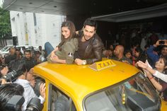 Alia Bhatt and Varun Dhawan posing on taxi Dial 022-28272727 to avail Topz Cab services