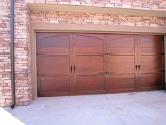 The cherry wood finish on this steel garage door adds a dynamic element to the house with the surrounding mixed colored brick.