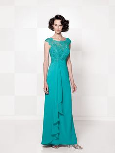 Chiffon mock-wrap dress with hand-beaded lace cap sleeves, bateau neck beaded lace over a sweetheart bodice with empire waistline, keyhole back, side gathered skirt with cascading ruffle and sweep train, suitable as a mother of the bride dress or formal gown. Matching shawl included.Sizes: 4 – 20