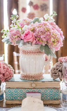 En cualquier decoración de estilo shabby chic hay ciertos complementos que no pueden faltar como juegos de café o té, velas, o jarrones antiguos que suelen utilizarse para tener flores en colores suaves como el rosa.