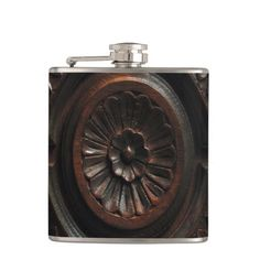 This eye-catching hip flask is decorated with a photographic image of a beautiful artistic wood carving in shades of brown, gold, mahogany and black. A central abstract circular flower pattern has petals radiating out to a carved circle with four sections on the back. Each section has abstract leaf carvings. Please note that it features a photographic image of wood #wood #flask #hipflask