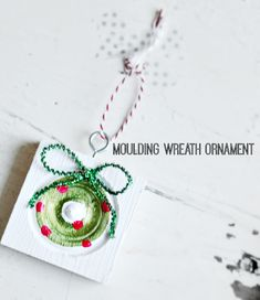 moulding wreath ornament....good base idea, I would embellish more (maybe add border around square, tie Christmas ribbons around eye hook, use punched red glitter paper for balls, use a red velvet bow for the wreath brow, etc.)