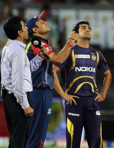 Former Indian cricketer and television presenter Sanjay Manjrekar (L), Delhi Daredevils captain Virender Sehwag (C), and Kolkata Knight Riders captain Gautam Gambhir look skywards during the coin toss of the IPL Twenty20 first playoff cricket match between Delhi Daredevils and Kolkata Knight Riders at The Subrata Roy Sahara Stadium in Pune on May 22, 2012.
