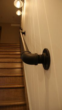 painted pipe handrail on wall at beginning of stairs