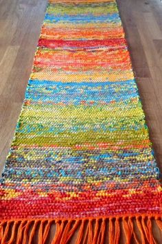 ZoZo Artwear by Lois Weaver: Easy Summer Weaving - Fabric Strip Table Runner - done on a RH loom.  Weft is a quilters Jelly Roll.  No further details, like if she cut the strips into thinner pieces.