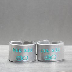"""These stamped sister rings make the perfect gift for your big or little sister, or even your daughters for a special gift. Features & Measurements: ♥ 14 Gauge Aluminum ♥ 1/2"""" Wide ♥ Easily Adjustable"""