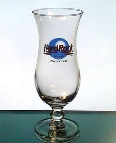 Hard Rock Cafe Whistler, BC, Canada Hurricane Glass Blue Logo Closed Collectible  Collectible Hard Rock Cafe Hurricane Glass from Whistler, Canada. Hard Rock Cafe Logo in orange lettering on blue background. Whistler is below it in black lettering. This is smaller than the typical hurricane style glassware.  This store was established 9/5/1995 and closed 6/1/2000. The only way to get a collectible glass from this one is via the secondary market online.